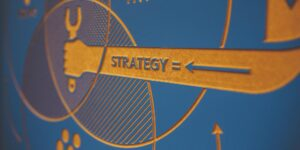 Image of a graphic showing an arm that says strategy on it holding a tool.