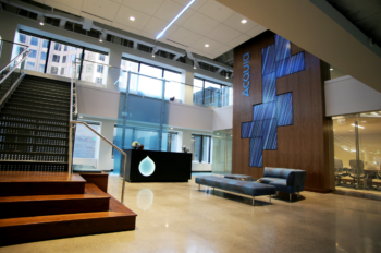 Lobby of Acquia with stairs to left and wall of screens to right