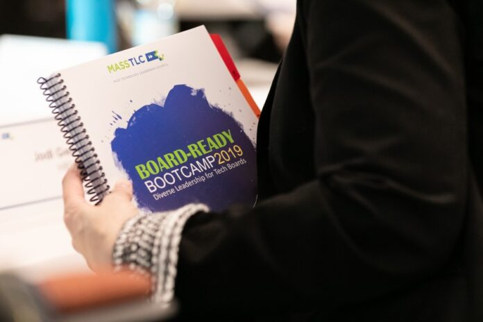 image showing person holding a Board Ready Bootcamp 2019 binder.