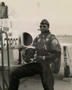 Chevy Cleaves in flight gear standing next to an airplane
