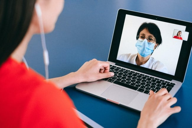 woman speaking with doctor over computer