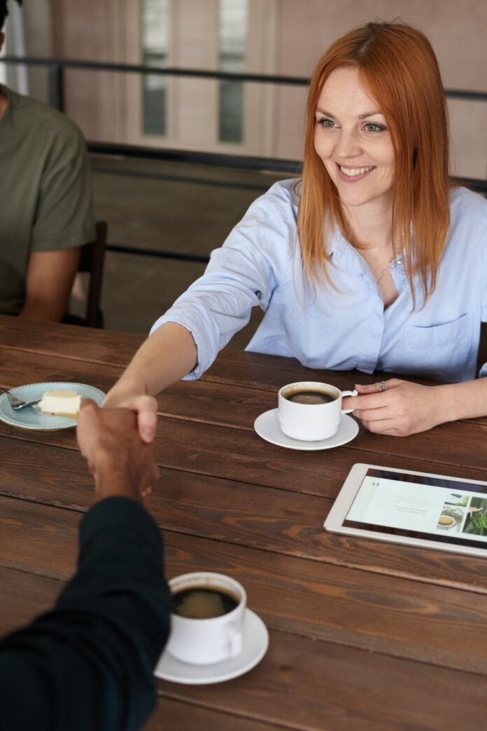 Image of a woman shaking hands over a table with coffee and a tablet