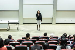 Image of woman speaking to people in a lecture hall.