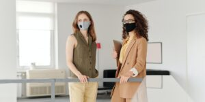 two professional women in masks talking