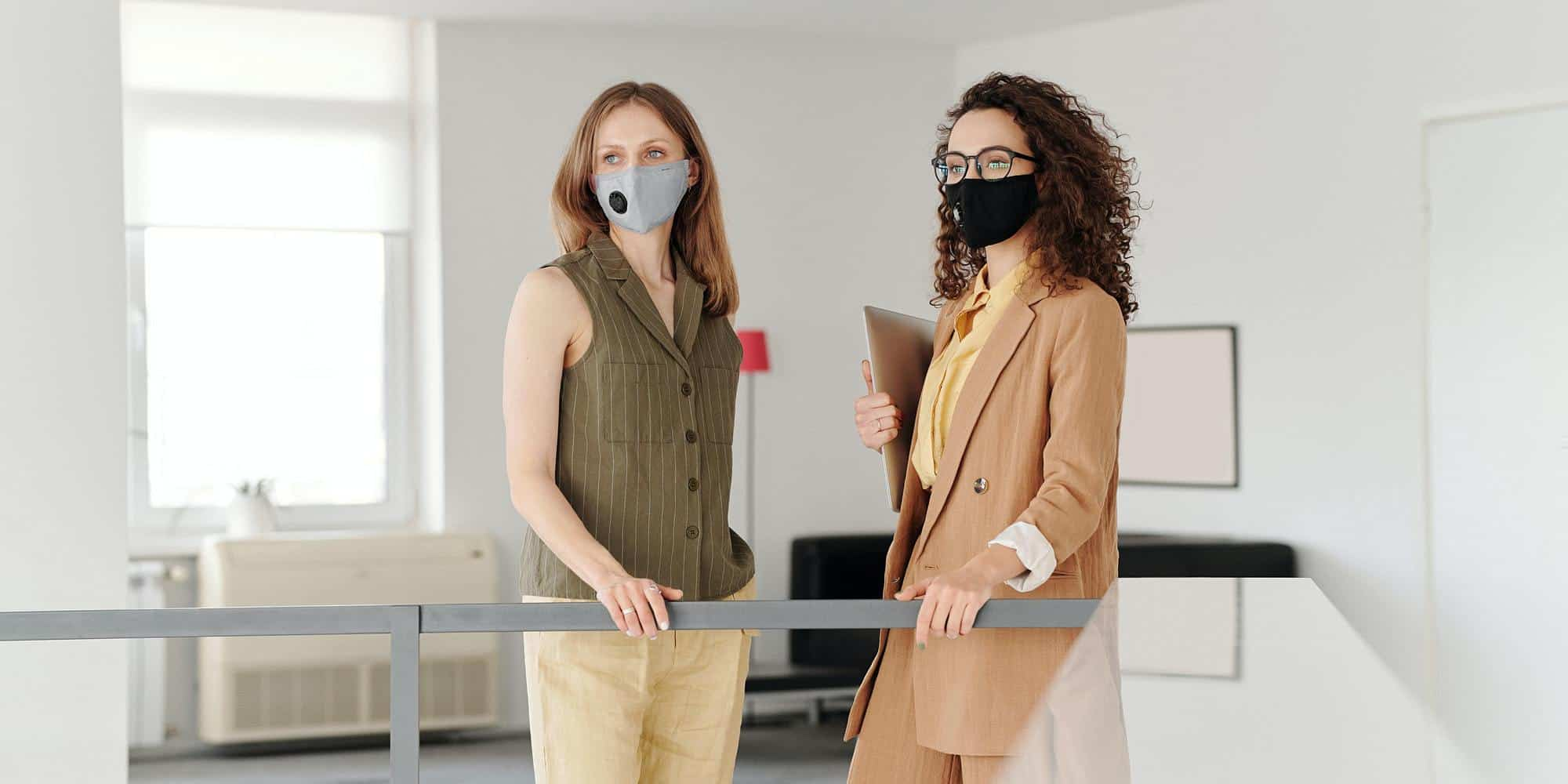 two professional women in masks talking
