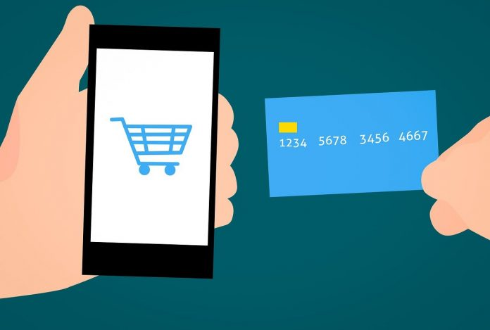Image: Graphic illustration of a hand holding a smart phone and another hand holding a blue credit card. The smart phone has a shopping cart pictured on it, implying that someone is using the credit card to complete a transaction online.