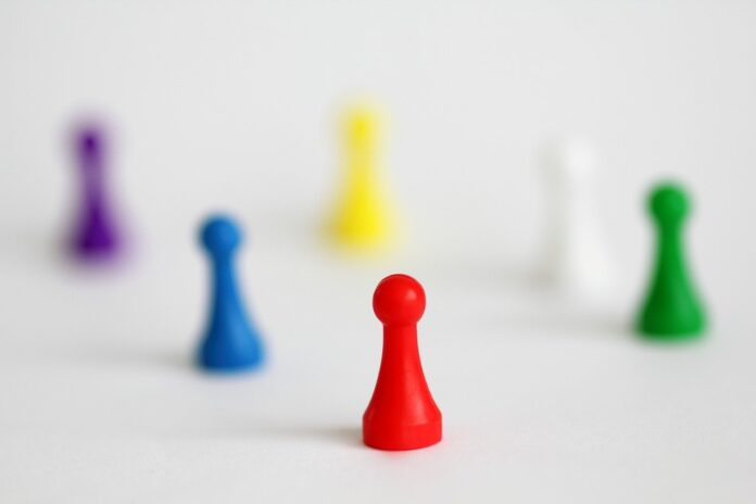 A purple, blue, red, yellow, white, and green gamepiece arranged on a white surface