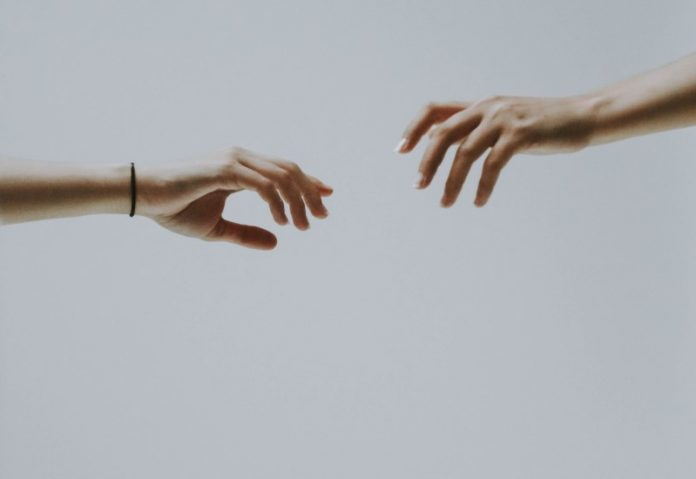Two hands stretching toward each other