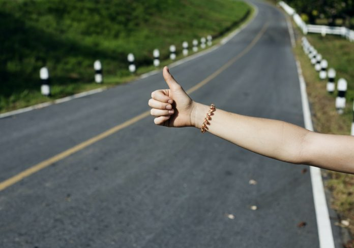 Road with woman's thumb raised to hitchhike
