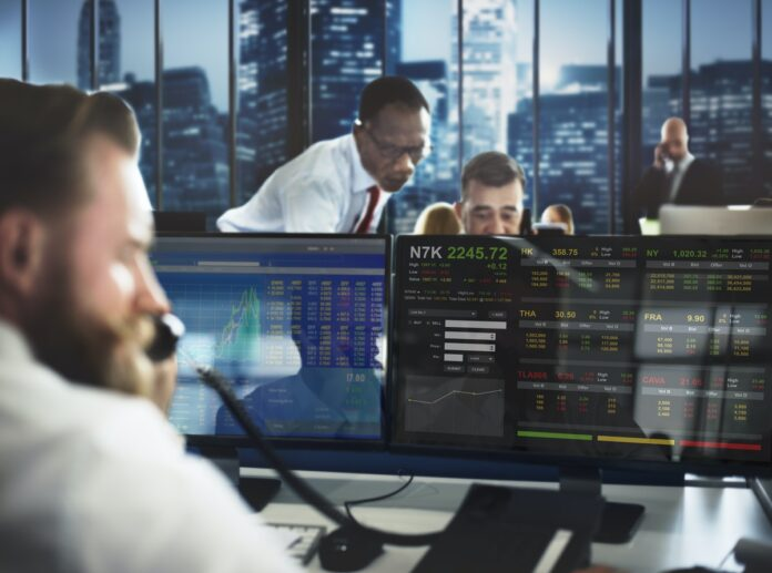 image showing stock traders on phones and in front of screens.