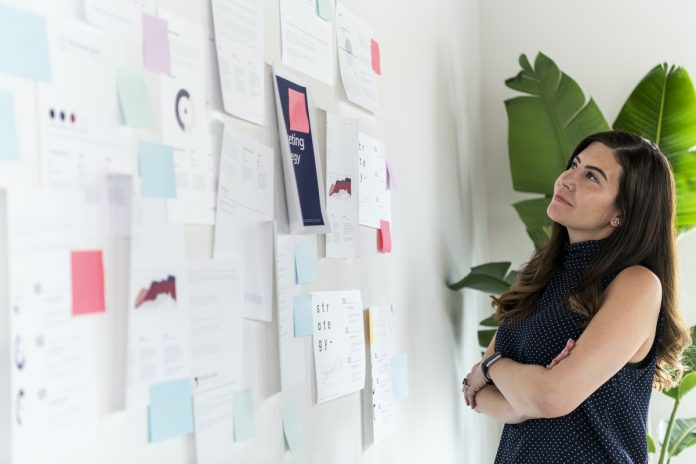 Woman looking at billboard with lots of work papers