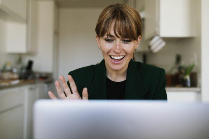 Woman sitting at computer waving to someone