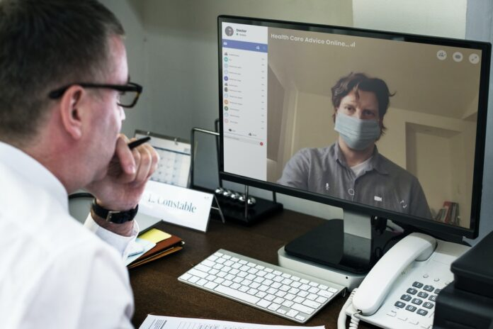 image showing man talking via computer to a man in a mask who appears on the monitor screen.