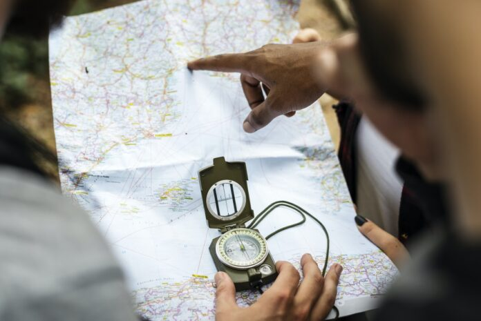People looking at map and holding compass