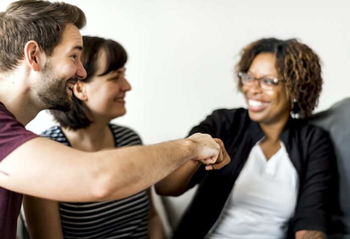 Image of three people smiling and fist bumping.