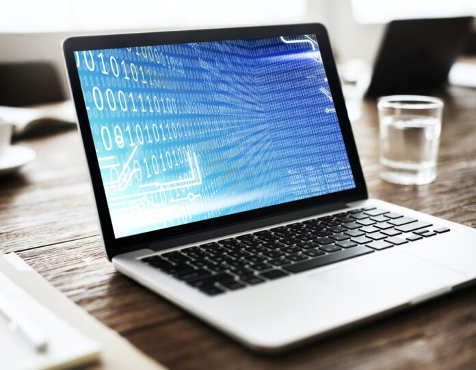 Laptop with binary code on screen sitting on table