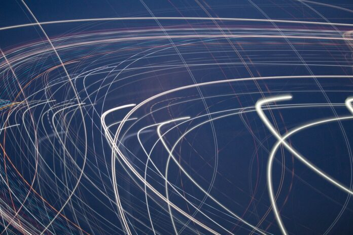 An abstract image of light beams curving in front of a navy background