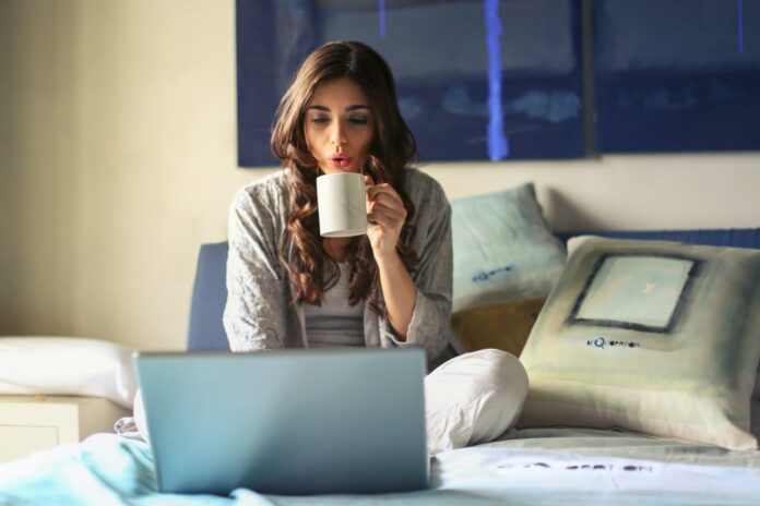 Image of a woman sitting on a bed with a computer blowing on a mug she is holding close to her face