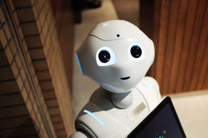 A white robot with large eyes is holding a smart tablet and looking up toward the camera.