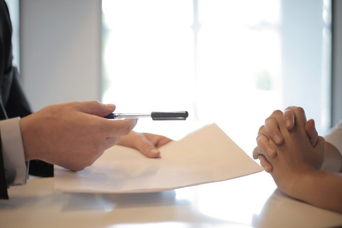 A person in a suit reaches out across a table with a pen and piece of paper in hand, asking the person across the table to sign. The person on the other side of the table has their hands clasped together.