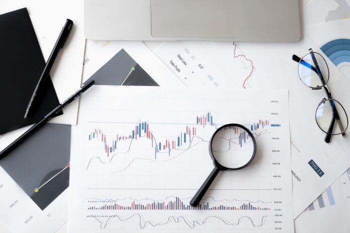 A magnifying glass over business charts on a desktop
