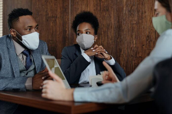 A man and two women wearing suits sit at a board room table wearing masks.