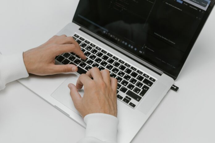 Hands typing on the keyboard of a laptop
