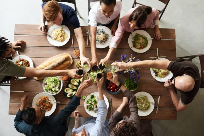 Aerial view of 8 people gathered around a table sharing a meal. There are full plates of food and everyone is reaching in to clink their glasses together.