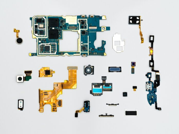 Computer chips of various shapes and sizes scattered on a white background