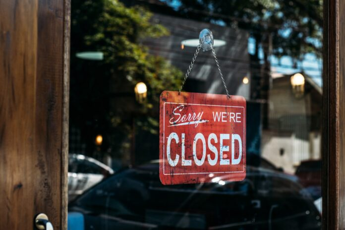 Image of Sorry We're Closed sign in a shop window