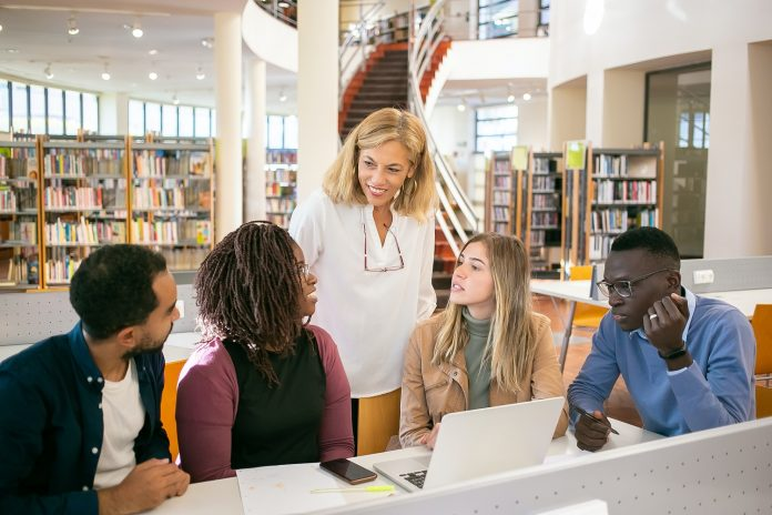 Four teen students sit in front of an open laptop in the library. An adult woman stands behind them and seems to be giving advice.