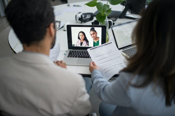 Two people seen from behind are speaking with two people on a virtual call on their laptops. One holds a piece of paper.