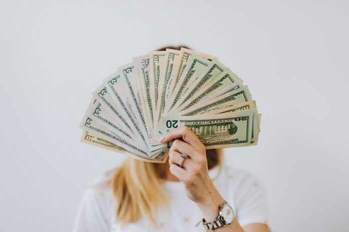 A person with long blond hair holds up a stack of various dollar bills arranged in a fan blocking their face