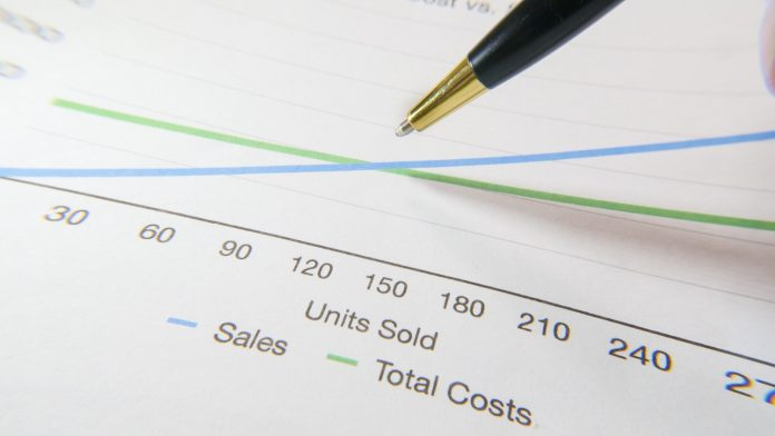 A close up shot of the tip of a pen hovering over a chart showing sales and total costs. One line is increasing steeply and the other is flat with a slight increase.