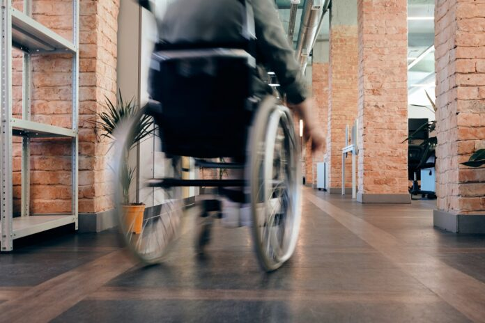 A photo of a person using a wheelchair, visible from the shoulders down