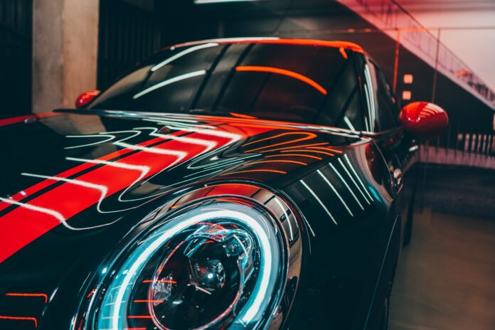 A black car reflects futuristic red and white light