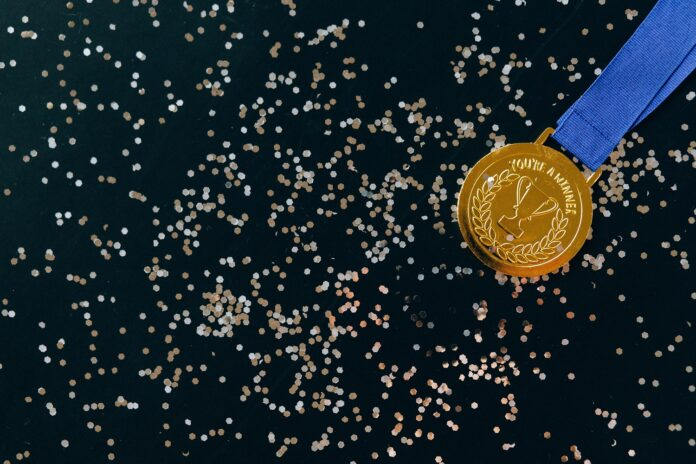 A gold medal tied to a blue ribbon and confetti on a black backdrop