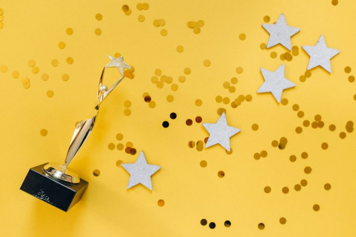 A trophy and some glitter and stars lie flat and scattered on a yellow background