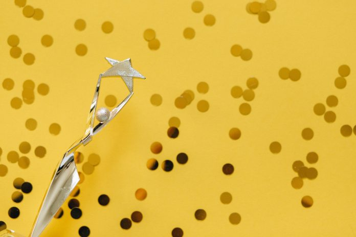 A gold trophy and gold confetti in front of a yellow background