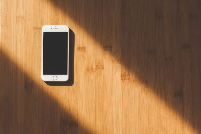 A white iphone with a blank, powered-off screen lays flat on a hardwood floor directly in a beam of light.