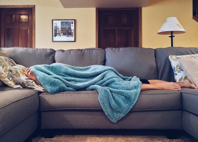 A person lies on a sofa underneath a blanket with their feet sticking out from underneath.