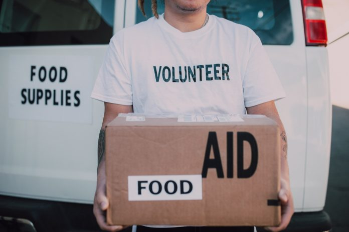 A pA person wearing a tshirt that says VOLUNTEER is holding a cardboard box that is laveled FOOD and AID. They are standing in front of a white van that says FOOD SUPPLIES.erson wearing a tshirt that says VOLUNTEER is holding a cardboard box that is laveled FOOD and AID. They are standing in front of a white van that says FOOD SUPPLIES.