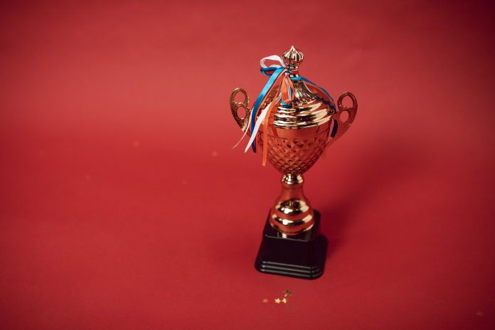 A small trophy cup with thin red, white, and blue ribbon against a red backdrop