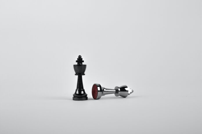 Two silver chess pieces on a white surface. One is knocked over on its side.