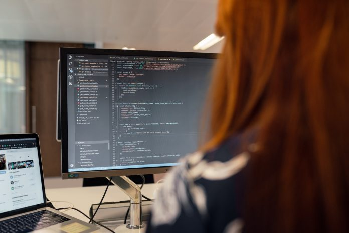 A woman with red hair sits at a desk. The focus is over her should at a desktop computer screen displaying lines of code. A laptop is open on her desk with Twitter visible.