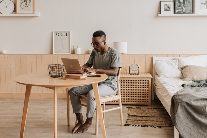 Image: A man in loungewear sits at a table next to a bed on his laptop. The room is dominated by neutral colors. The man is working from home.
