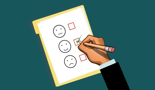 graphic image of hand holding pencil and checking off a box in list of three faces: neutral, happy, sad