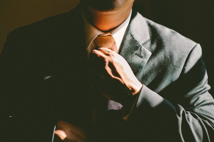 A man in a suit sits in the shadows with his face hidden.