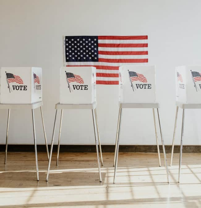 Image of four voting booths with an American flag on the wall behind.